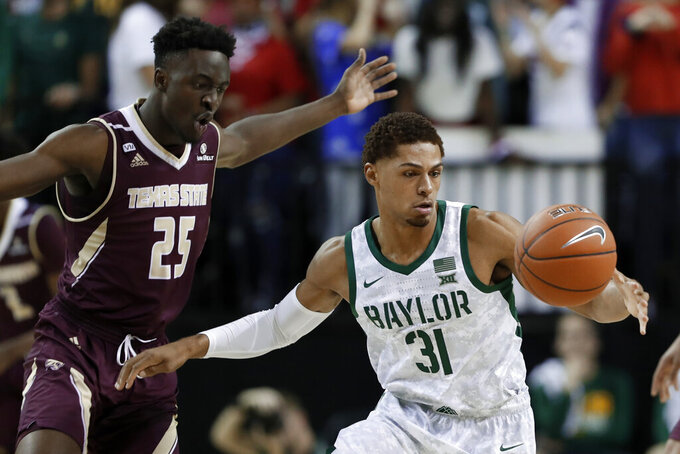 Texas State forward Alonzo Sule (25) loses control of the ball to Baylor guard MaCio Teague (31) during the first half of an NCAA college basketball game in Waco, Texas, Friday, Nov. 15, 2019. (AP Photo/Tony Gutierrez)