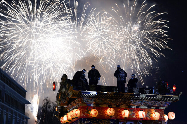 In this Tuesday, Dec. 3, 2019, photo, men stand on top of a lantern-covered float as fireworks light up the sky during the Chichibu Night Festival in Chichibu, north of Tokyo, Japan. Moving six towering floats up a hill and into the town center is the culminating moment of a Shinto festival that has evolved from a harvest thanksgiving into a once-a-year meeting between two local gods. (AP Photo/Toru Hanai)
