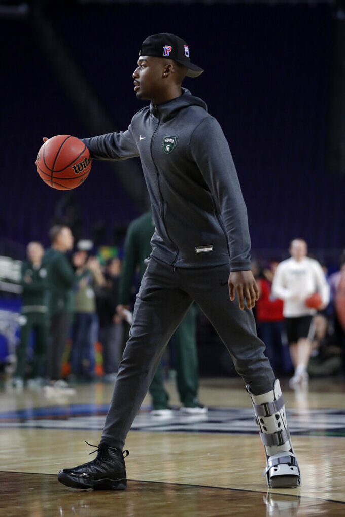 Injured Michigan State guard Joshua Langford dribbles on the court during a practice session for the semifinals of the Final Four NCAA college basketball tournament, Friday, April 5, 2019, in Minneapolis. (AP Photo/Jeff Roberson)