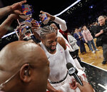 Miami Heat players dump water onto teammate Dwyane Wade, center, during his interview following the final NBA basketball game of Wade's career, against the Brooklyn Nets on Wednesday, April 10, 2019, in New York. (AP Photo/Kathy Willens)