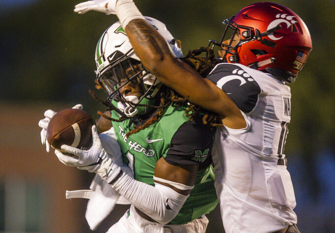 Marshall wide receiver Willie Johnson, left, makes a catch against Cincinnati's Taj Ward an NCAA college football game on Saturday, Sept. 28, 2019, in Huntington, W.Va. (Sholten Singer/The Herald-Dispatch via AP)
