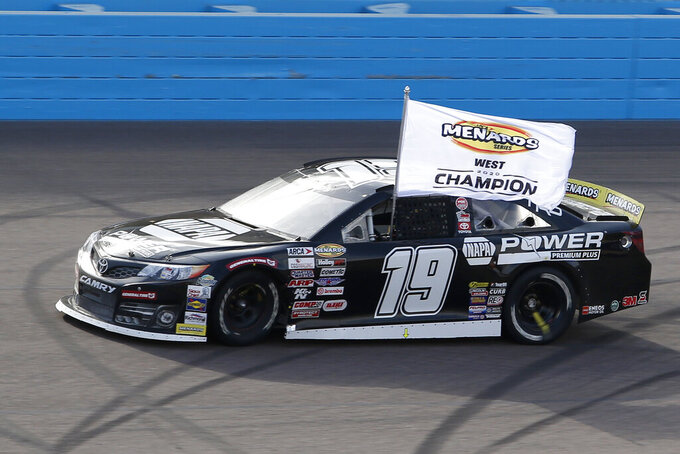 Jesse Love displays a season champion banner out of his race car as he circles the track following the ARCA Series auto race at Phoenix Raceway, Saturday, Nov. 7, 2020, in Avondale, Ariz. (AP Photo/Ralph Freso)