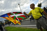 A man holds a Ikurrina or Basque flag close to Catalonia independence flag or ''Estelada'', during a protest by Basque pro-independence activists in support of Catalonia's independence movement following Spain's conviction of Catalan separatist leaders, in San Sebastian, northern Spain, Saturday, Oct. 19, 2019. Spain's Supreme Court on October 14 sentenced 12 prominent former Catalan politicians and activists of illegally promoting the Catalonia region's independence. (AP Photo/Alvaro Barrientos)