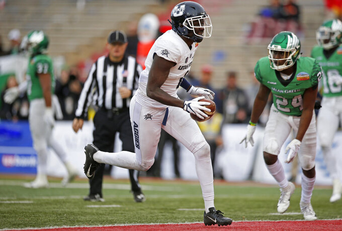 Utah State wide receiver Ron'quavion Tarver (1) scores a touchdown during the second half of the New Mexico Bowl NCAA college football game against North Texas in Albuquerque, N.M., Saturday, Dec. 15, 2018. Utah State won 52-13. (AP Photo/Andres Leighton)