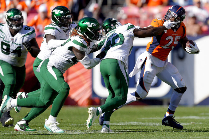 Denver Broncos running back Melvin Gordon (25) eludes the tackle of New York Jets free safety Marcus Maye (20) during the second half of an NFL football game, Sunday, Sept. 26, 2021, in Denver. (AP Photo/David Zalubowski)