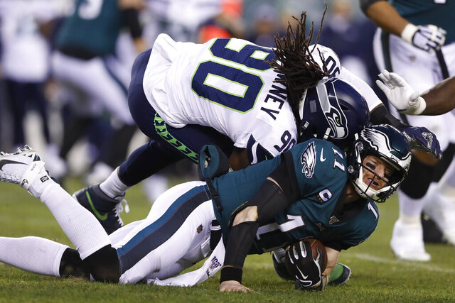 Seattle Seahawks' Jadeveon Clowney (90) hits Philadelphia Eagles' Carson Wentz (11) during the first half of an NFL wild-card playoff football game, Sunday, Jan. 5, 2020, in Philadelphia. (AP Photo/Julio Cortez)