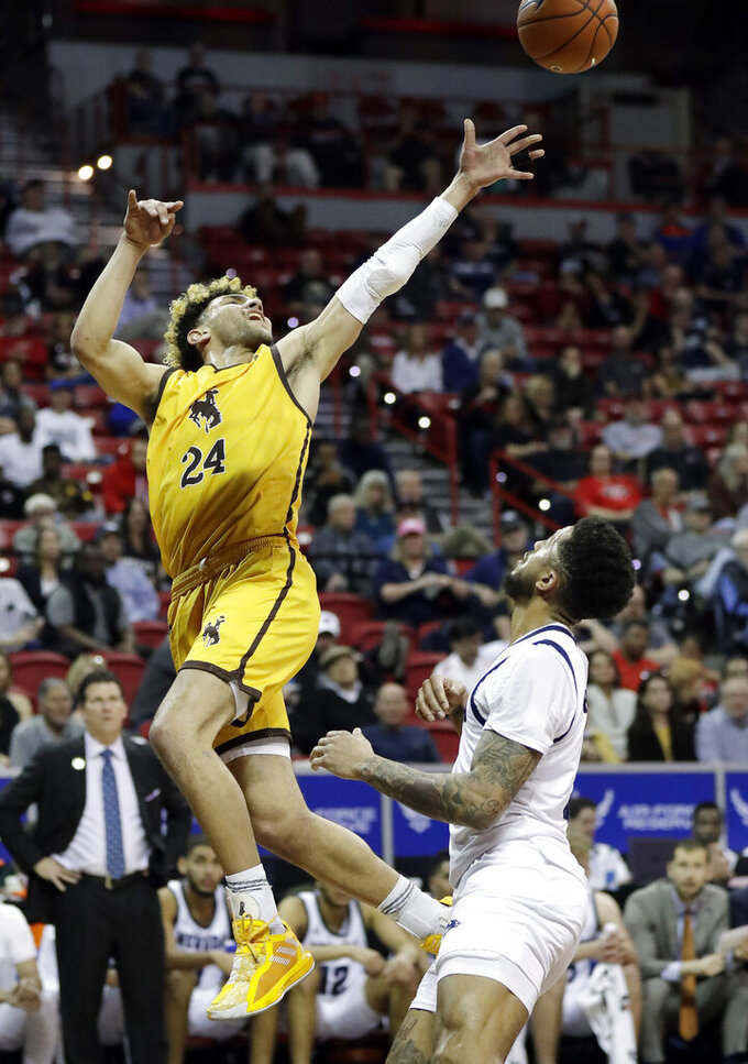 Wyoming's Hunter Maldonado shoots as Nevada's Jalen Harris defends during the first half of a Mountain West Conference tournament NCAA college basketball game Thursday, March 5, 2020, in Las Vegas. (AP Photo/Isaac Brekken)