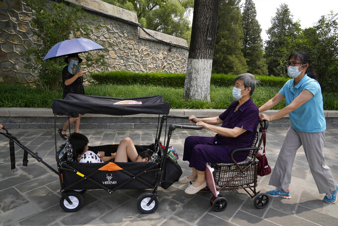 Tourists wear face masks as they visit the Summer Palace in Beijing Tuesday, Aug. 3, 2021. The current coronavirus outbreaks in China, while still in the hundreds of cases in total, have spread much more widely than previous ones, reaching multiple provinces and cities including the capital, Beijing. Many of the cases have been identified as the highly contagious delta variant that is driving a resurgence in many countries. (AP Photo/Ng Han Guan)