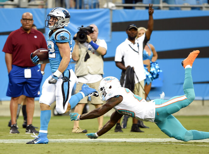 Carolina Panthers' Christian McCaffrey, left, runs past Miami Dolphins' T.J. McDonald, right, for a touchdown in the first half of a preseason NFL football game in Charlotte, N.C., Friday, Aug. 17, 2018. (AP Photo/Mike McCarn)