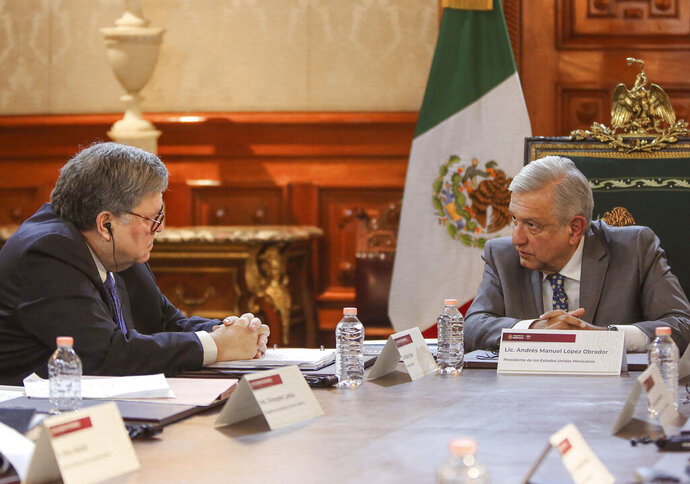 In this photo provided by the Mexican presidential press office, U.S. Attorney General William Barr, left, speaks with Mexican President Andres Manuel Lopez Obrador at the National Palace in Mexico City, Thursday, Dec. 5, 2019. The closed-door meeting came about a week after U.S. President Donald Trump suggested his government could classify Mexican cartels as terrorist organizations. (Mexican presidential press office via AP)