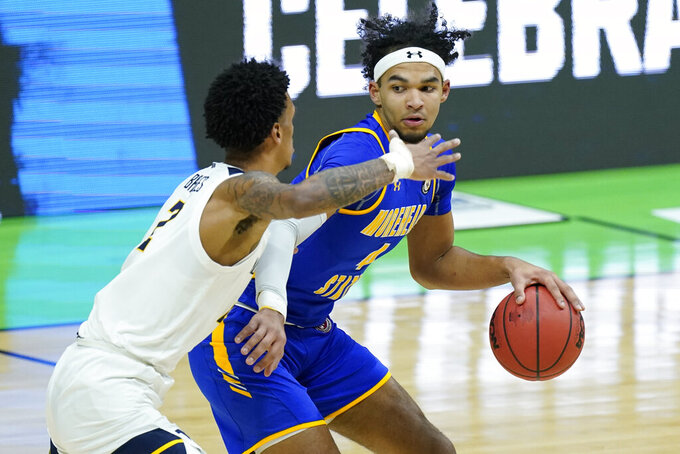 Morehead State's Johni Broome, right, is guarded by West Virginia's Jalen Bridges (2) during the first half of a college basketball game in the first round of the NCAA tournament at Lucas Oil Stadium Friday, March 19, 2021, in Indianapolis. (AP Photo/Mark Humphrey)