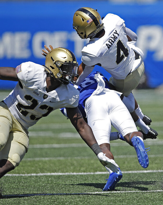 Army quarterback Christian Anderson (4) is upended by Georgia State's Chris Moore, center, during the first half of an NCAA football game Saturday, Sept. 4, 2021, in Atlanta. At left is Army running back Anthony Adkins. (AP Photo/Ben Margot)
