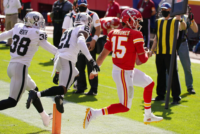 Kansas City Chiefs quarterback Patrick Mahomes (15) scores on a 3-yard touchdown run ahead of Las Vegas Raiders safety Jeff Heath (38) and cornerback Amik Robertson (21) during the first half of an NFL football game, Sunday, Oct. 11, 2020, in Kansas City. (AP Photo/Charlie Riedel)