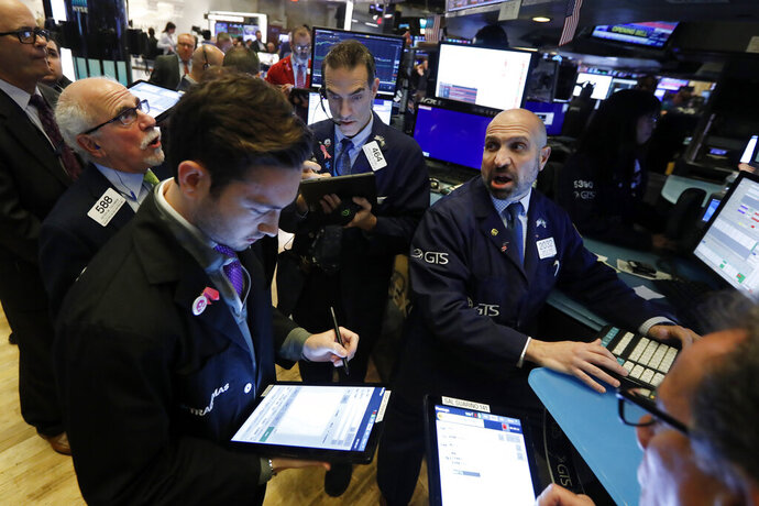 FILE - In this Nov. 14, 2019, file photo specialist James Denaro, right, works with traders at his post on the floor of the New York Stock Exchange. The U.S. stock market opens at 9:30 a.m. EST on Monday, Dec. 2. (AP Photo/Richard Drew, File)