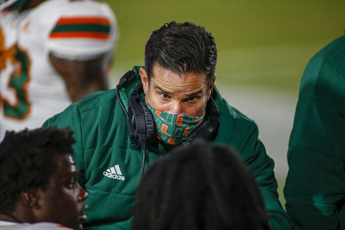Miami coach Manny Diaz talks to his team during the first quarter against Duke in an NCAA college football game Saturday, Dec. 5, 2020, in Durham, N.C. (Nell Redmond/Pool Photo via AP)