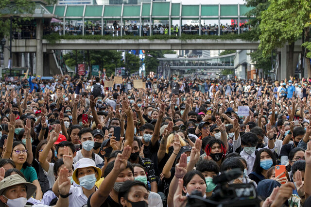 Pro-democracy protesters flash three-fingered salute during a protest as they occupied a main road at the central business district in Bangkok, Thailand, Thursday, Oct. 15, 2020. Thailand's government declared a strict new state of emergency for the capital on Thursday, a day after a student-led protest against the country's traditional establishment saw an extraordinary moment in which demonstrators heckled a royal motorcade. (AP Photo/Gemunu Amarasinghe)