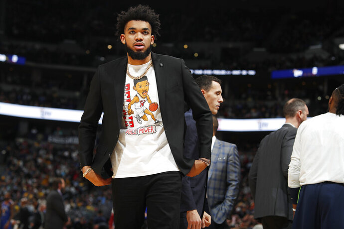 Minnesota Timberwolves center Karl-Anthony Towns takes a seat on the bench in the second half of an NBA basketball game against the Denver Nuggets, Friday, Dec. 20, 2019, in Denver. Towns, who usually starts for the Timberwolves, did not play because of an ankle injury. (AP Photo/David Zalubowski)