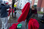 Demonstrators protest against the president of the Philippines and the bloodshed on his war on drugs by tying hundreds of strips of red cloth to the trees and signs outside of the Philippines Embassy in Washington, Wednesday, Feb. 13, 2019. In the nation's capital, it can be hard for protesters to stand out. Fifty people _ or even 500 _ holding signs and shouting hardly merits a second glance in this city of protests. That's why Washington activists have to get creative. (AP Photo/Jose Luis Magana)