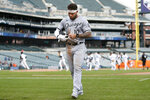 Chicago White Sox's Yoan Moncada walks off the field as the Detroit tigers celebrate a 5-3 win in a baseball game Tuesday, Sept. 21, 2021, in Detroit. (AP Photo/Duane Burleson)