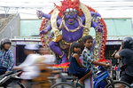 Children on their bicycle move past a giant effigy locally known as