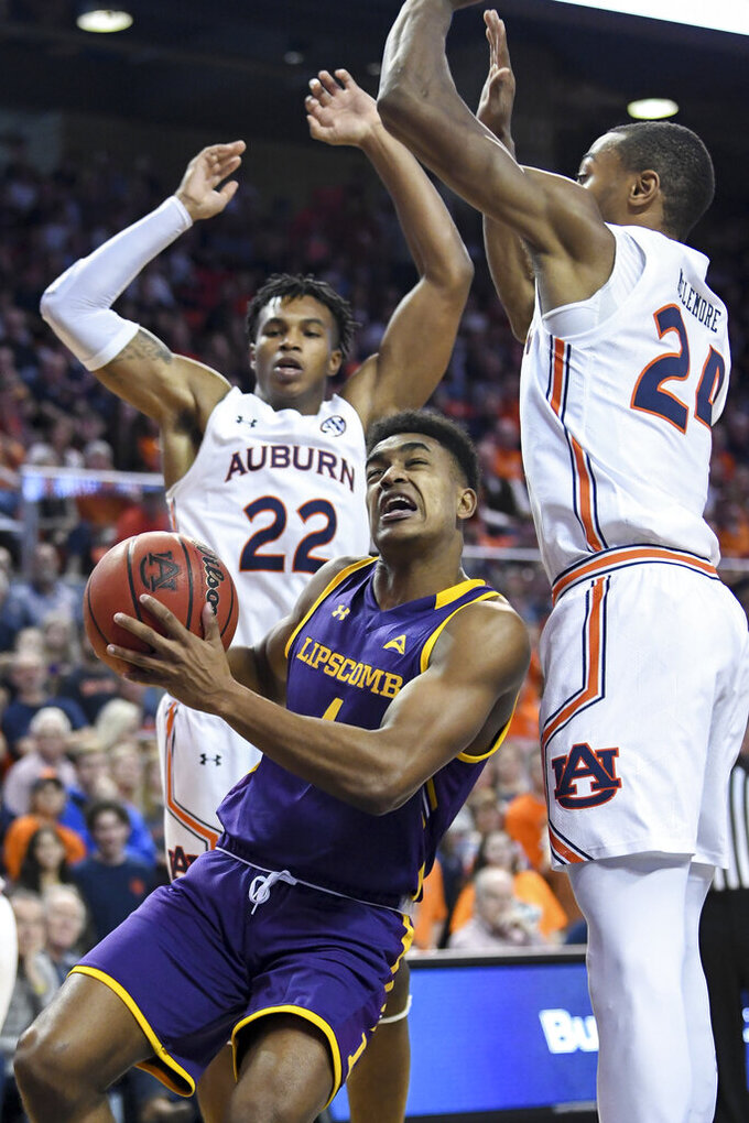 Lipscomb guard Greg Jones (1) looks to shoot while defended by Auburn forward Anfernee McLemore (24) and guard Allen Flanigan (22) during the first half of an NCAA college basketball game Sunday, Dec. 29, 2019, in Auburn, Ala. (AP Photo/Julie Bennett)