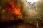 Firefighters battle the Morton Fire as it consumes a home near Bundanoon, New South Wales, Australia, Thursday, Jan. 23, 2020. (AP Photo (AP Photo/Noah Berger)