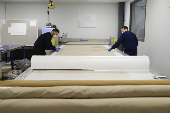 Dallara USA employees Michael Carlisle, left, and Marty Bigley cut out material patterns for protective medical gowns, during the coronavirus pandemic Wednesday, April 15, 2020, in Indianapolis. (AP Photo/Darron Cummings)