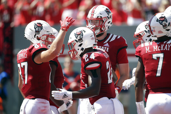 North Carolina State running back Zonovan Knight (24) is congratulated by wide receiver Thayer Thomas (87) following Knight's touchdown during the first half of an NCAA college football game against East Carolina in Raleigh, N.C., Saturday, Aug. 31, 2019. (AP Photo/Gerry Broome)