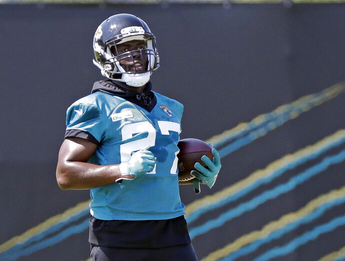 Jacksonville Jaguars running back Leonard Fournette (27) carries the ball during an NFL football practice, Tuesday, May 21, 2019, in Jacksonville, Fla. (AP Photo/John Raoux)