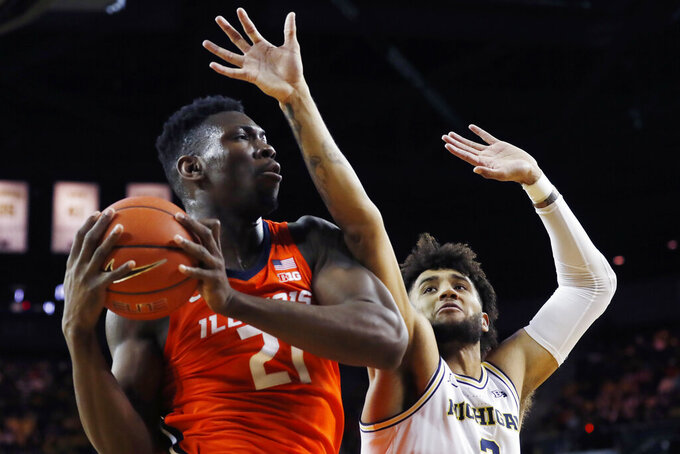 Illinois center Kofi Cockburn, left, grabs a rebound next to Michigan forward Isaiah Livers, right, during the first half of an NCAA college basketball game, Saturday, Jan. 25, 2020, in Ann Arbor, Mich. (AP Photo/Carlos Osorio)