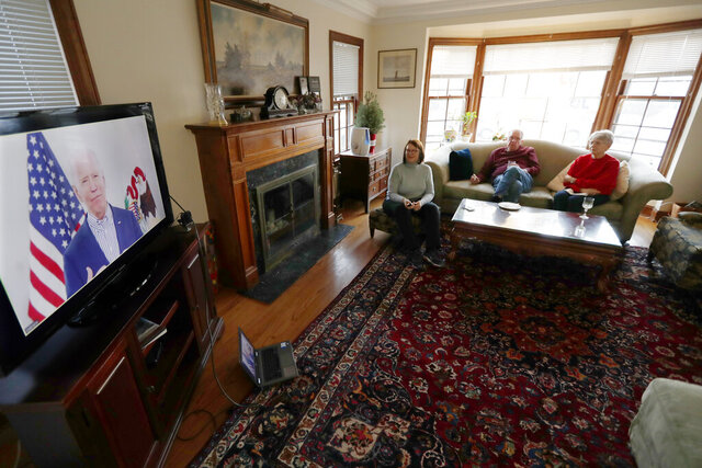 Lally Doerrer, left, and neighbors Douglas and Marlene Groll, watch Joe Biden during his Illinois virtual town hall, in her living room Friday, March 13, 2020, in Chicago. (AP Photo/Charles Rex Arbogast)