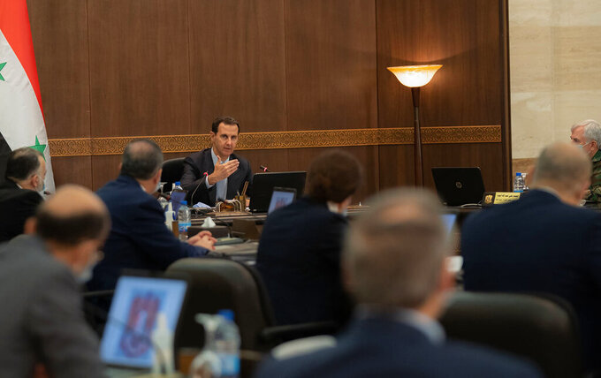 In this photo released on the official Facebook page of the Syrian Presidency, Syrian President Bashar Assad, center, heads a cabinet meeting, in Damascus, Syria, Tuesday, March 30, 2021. Assad and his wife have recovered from COVID-19 and returned to their regular duties on Tuesday, three weeks after they had tested positive for the coronavirus, the president's office said. (Syrian Presidency Facebook page via AP)