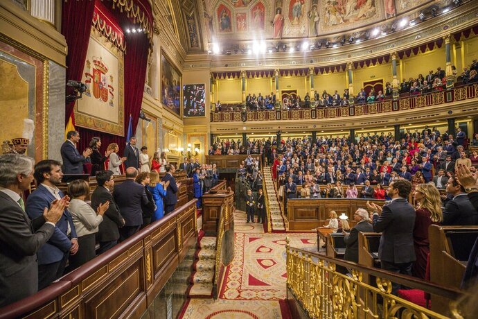 Members of the Spanish parliament applaud Spain's King Felipe VI, left, after giving a speech during the official opening of the parliamentary season in Madrid, Monday, Feb. 2, 2020. Nearly 50 lawmakers who advocate for the Spanish regions to become independent have boycotted Monday's ceremonial opening of the nation's legislative season over the presence of the royal family. The representatives of five parties from the Catalonia, Basque Country and Galicia regions, all in northern Spain, say the king's figure is