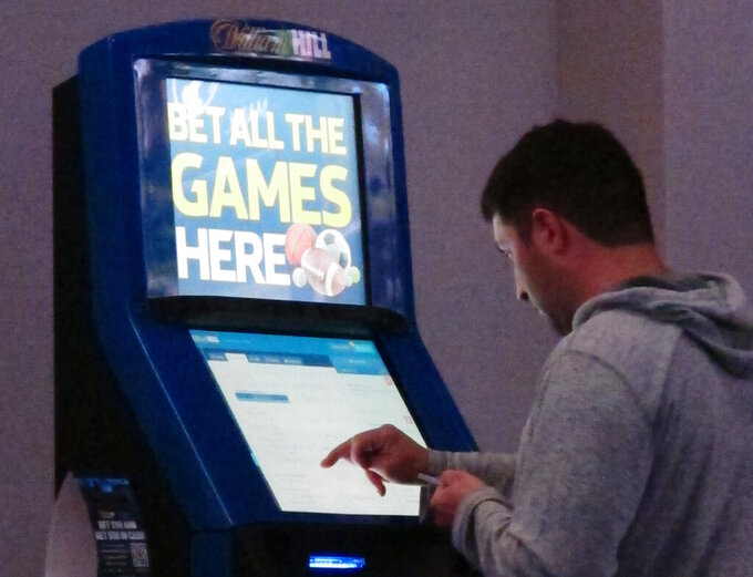 FILE - This June 21, 2019, file photo shows a person making bets at a William Hill kiosk inside the Ocean Casino Resort in Atlantic City, N.J. A national group that fights compulsive gambling is concerned about financial deals between colleges and sports betting companies. Last September, PointsBet and the University of Colorado inked a $1.6 million five-year deal in which the school will receive funding while promoting the sports book on its media channels and at in-person sporting events. The deal also calls for Colorado to receive $30 for each person that signs up for sports betting after being referred by the school. (AP Photo/Wayne Parry, File)