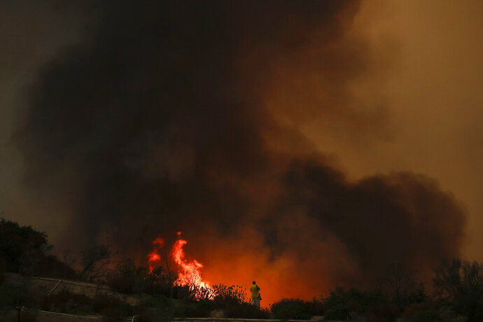 FILE - In this Aug. 8, 2018, file photo, a photographer takes pictures of a wildfire burning near a residential area in Lake Elsinore, Calif. Photographers have captured searing, intimate images of active and dangerous wildfires burning California, due in large part to a state law that guarantees press virtually unfettered access to disaster sites. That's not the case everywhere as rules about media access vary by state, and even by government agency.  (AP Photo/Jae C. Hong, File)