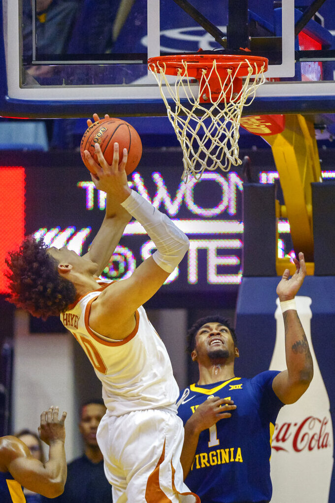West Virginia forward Derek Culver (1) tries to block Texas forward Jaxson Hayes (10)  who shoots during the second half of an NCAA college basketball game in Morgantown, W.Va., Saturday, Feb. 9, 2019. (AP Photo/Craig Hudson)