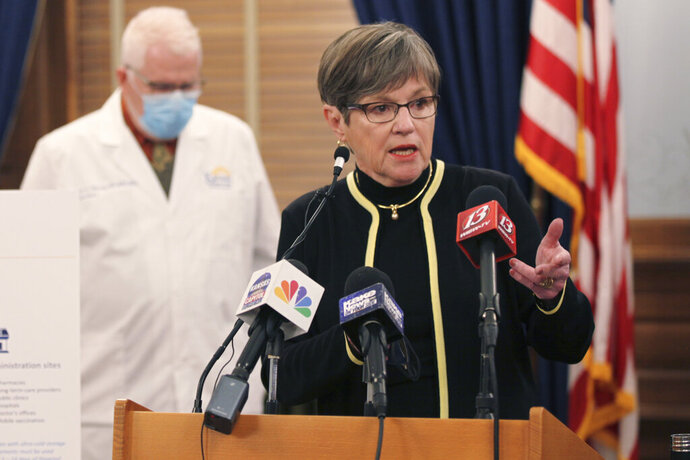 Kansas Gov. Laura Kelly answers questions from reporters during a news conference in which she announces that the state will shut down its system for processing unemployment claims to combat fraud, Wednesday, Jan. 27, 2021, at the Statehouse in Topeka, Kan. The 2 1/2-day shutdown will delay payments to some jobless workers while the state installs anti-fraud processes. (AP Photo/John Hanna)
