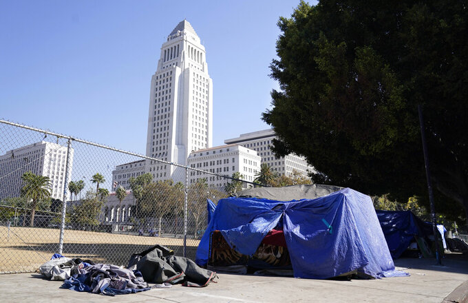 FILE - In this Oct. 28, 2020, file photo, a homeless person's tent stands just outside Grand Park with Los Angeles City Hall in the background in Los Angeles. Faced with an out-of-control homeless crisis, On Monday, April 19, 2021, Los Angeles Mayor Eric Garcetti announced plans to spend nearly $1 billion in the coming year in hopes of getting tens of thousands of unhoused people off the streets. (AP Photo/Chris Pizzello, File)