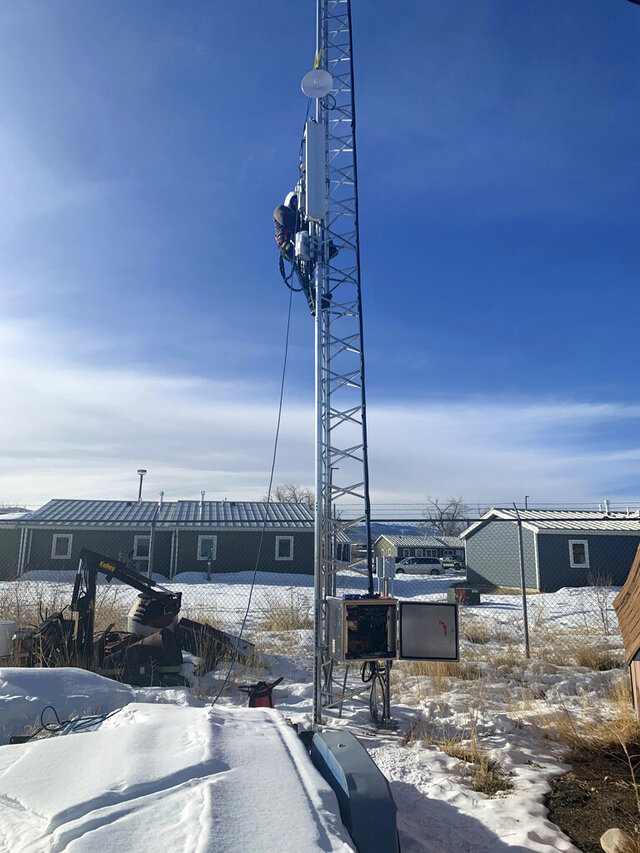 In this photo provided by Mariel Triggs and taken Jan. 17, 2020, Patrick Lawson, executive manager of the Northern Arapaho Tribal Industries/Wind River Internet, tests broadband equipment in Fort Washakie on the Wind River Indian Reservation in Wyoming. (Mariel Triggs via AP)