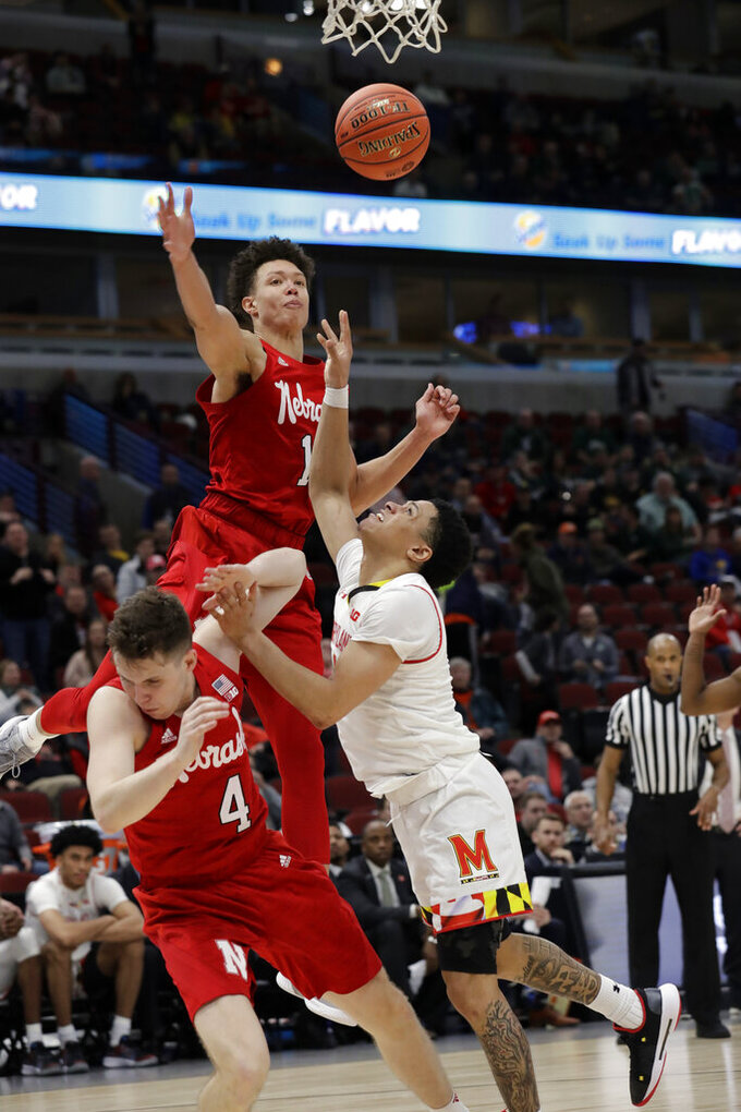 Maryland's Anthony Cowan Jr. takes a shot against Nebraska's Johnny Trueblood (4) and Isaiah Roby (15) during the second half of an NCAA college basketball game in the second round of the Big Ten Conference tournament, Thursday, March 14, 2019, in Chicago. The Nebraska won 69-61. (AP Photo/Nam Y. Huh)