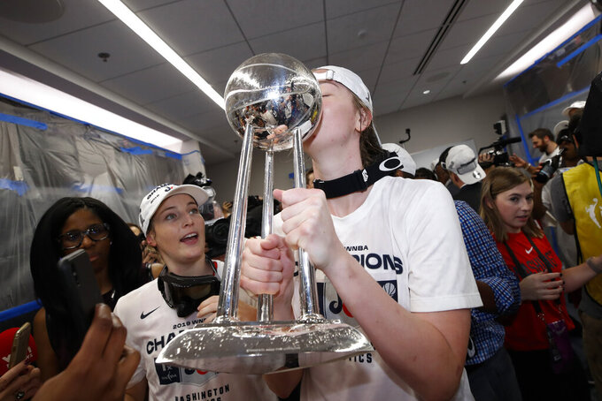 FILE - In this Oct. 10, 2019, file photo, Washington Mystics center Emma Meesseman kisses the trophy in the locker room after Game 5 of basketball's WNBA Finals against the Connecticut Sun in Washington. Washington was so bad for so long in the major professional sports but maybe soon it will be said that D.C. stands for District of Champions. The Nationals are in the city's first World Series in 86 years. The Mystics recently won the WNBA championship. And the Capitals won the Stanley Cup in 2018. Before that, the nation's capital endured a 26-year championship drought across MLB, NFL, NBA and NHL. (AP Photo/Alex Brandon, File)