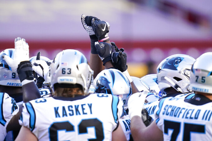 Members of the Carolina Panthers huddling before the start of an NFL Football Game against the Washington Football Team, Sunday, Dec. 27, 2020, in Landover, Md. (AP Photo/Carolyn Kaster)