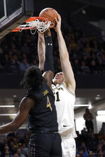 Michigan forward Austin Davis, right, dunks against Northwestern forward Jared Jones during the first half of an NCAA college basketball game in Evanston, Ill., Wednesday, Feb. 12, 2020. (AP Photo/Nam Y. Huh)