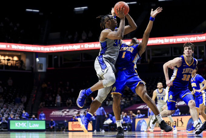 Creighton guard Denzel Mahoney, left, drives to the basket and is fouled by Xavier guard Paul Scruggs during the second half of an NCAA college basketball game Saturday, Feb. 27, 2021, in Cincinnati. Xavier won 77-69. (AP Photo/Aaron Doster)