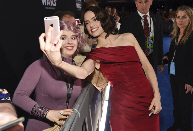Daisy Ridley, right, takes a selfie with a fan as she arrives at the world premiere of