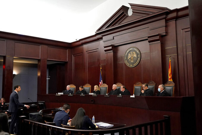 Attorney Dominic Draye, left, presents oral arguments before the Arizona Supreme Court, Tuesday, April 20, 2021, in Phoenix. The Arizona Supreme Court heard an expedited constitutional challenge to a new voter-approved tax on high-earning Arizonans designed to boost school funding on Tuesday. (AP Photo/Matt York)