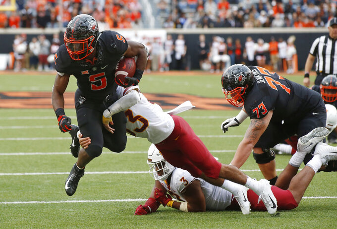 Oklahoma State running back Justice Hill (5) fights a tackle by Iowa State defensive back Braxton Lewis (33) in the second half of an NCAA college football game in Stillwater, Okla., Saturday, Oct. 6, 2018. (AP Photo/Sue Ogrocki)