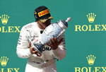 Mercedes driver Lewis Hamilton of Britain kisses the trophy as he celebrates on the podium after winning the Hungarian Formula One Grand Prix at the Hungaroring racetrack in Mogyorod, northeast of Budapest, Hungary, Sunday, Aug. 4, 2019. (AP Photo/Laszlo Balogh)