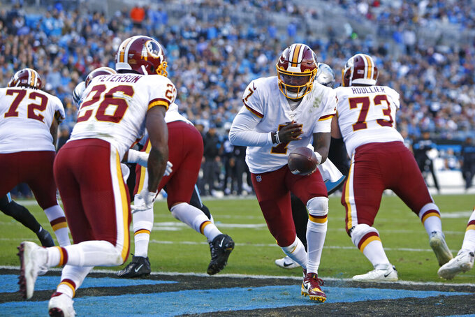 Washington Redskins quarterback Dwayne Haskins (7) hands off to running back Adrian Peterson (26) during the second half of an NFL football game against the Carolina Panthers in Charlotte, N.C., Sunday, Dec. 1, 2019. (AP Photo/Brian Blanco)