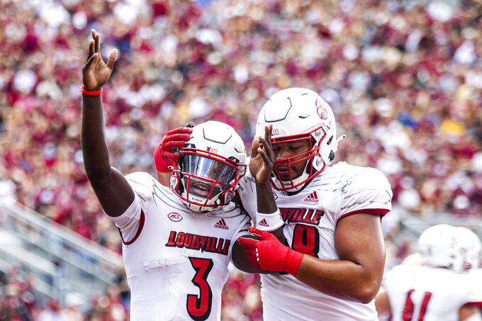 Louisville offensive lineman Michael Gonzalez, right, celebrates with quarterback Malik Cunningham after Cunningham scored a touchdown in the first half of an NCAA college football game against Florida State in Tallahassee, Fla., Saturday, Sept. 25, 2021. (AP Photo/Mark Wallheiser)